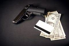 Κλείστε επάνω τα χρήματα με το πυροβόλο όπλο στο μαύρο υπόβαθρο Στοκ Φωτογραφία