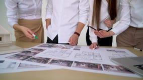 Κλείστε επάνω τεσσάρων αρχιτεκτόνων που συζητούν το σχέδιο μαζί στο γραφείο με τα σχεδιαγράμματα απόθεμα βίντεο