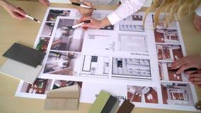 Κλείστε επάνω τεσσάρων αρχιτεκτόνων που συζητούν το σχέδιο μαζί στο γραφείο με τα σχεδιαγράμματα φιλμ μικρού μήκους
