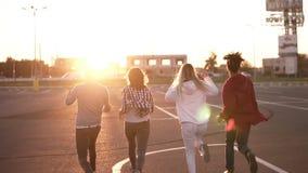 Κλείστε επάνω τεσσάρων μοντέρνων φίλων τρέχει από την κενή ζώνη χώρων στάθμευσης υπαίθρια - η ευτυχία διασκέδασης, οι νεαροί άνδρ απόθεμα βίντεο