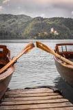 Κλείστε επάνω την άποψη σχετικά με τις όμορφες ξύλινες επίπεδες βάρκες κωπηλασίας με τα κουπιά στη λίμνη που αιμορραγείται, Σλοβε στοκ φωτογραφία