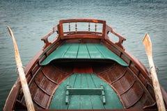 Κλείστε επάνω την άποψη σχετικά με την όμορφη ξύλινη επίπεδη βάρκα κωπηλασίας με τα κουπιά στη λίμνη που αιμορραγείται, Σλοβενία, στοκ εικόνες
