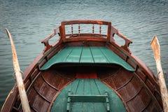 Κλείστε επάνω την άποψη σχετικά με την όμορφη ξύλινη επίπεδη βάρκα κωπηλασίας με τα κουπιά στη λίμνη που αιμορραγείται, Σλοβενία, στοκ φωτογραφία