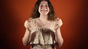 Κλείστε επάνω την άποψη της εύθυμης γυναίκας ανοίγει το πρόσωπό της παρουσιάζοντας μορφασμούς πέρα από το πορτοκαλί υπόβαθρο απόθεμα βίντεο