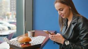 Κλείστε επάνω την άποψη του αρκετά νέου καφέ κατανάλωσης επιχειρηματιών και αποστολή των μηνυμάτων με το κινητό τηλέφωνό της ενώ  απόθεμα βίντεο