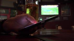 Κλείστε επάνω την άποψη του ατόμου χρησιμοποιώντας Samrtphone πίνοντας την μπύρα στο μπαρ φιλμ μικρού μήκους
