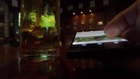 Κλείστε επάνω την άποψη του ατόμου χρησιμοποιώντας Samrtphone πίνοντας την μπύρα στο μπαρ απόθεμα βίντεο
