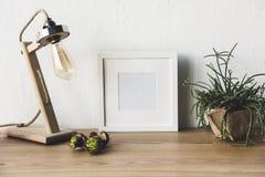 κλείστε επάνω την άποψη του κενού πλαισίου φωτογραφιών, του επιτραπέζιου λαμπτήρα και των εγκαταστάσεων flowerpot στοκ εικόνα