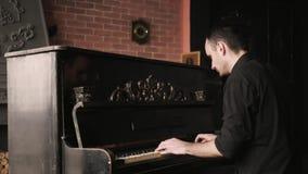 Κλείστε επάνω την άποψη του pianist που παίζει το πιάνο σε ένα ντεμοντέ σπίτι απόθεμα βίντεο