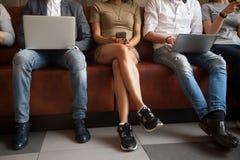 Κλείστε επάνω την άποψη των διαφορετικών ανθρώπων που κάθονται χρησιμοποιώντας τις ηλεκτρονικές συσκευές Στοκ Εικόνα