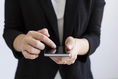Κλείστε επάνω την άποψη των χεριών επιχειρησιακών γυναικών δακτυλογραφώντας στο έξυπνο τηλέφωνό της indoors lifestyles Άσπρα υπόβ στοκ εικόνα με δικαίωμα ελεύθερης χρήσης