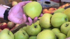 Κλείστε επάνω την άποψη των χεριών νεαρών άνδρων επιλέγοντας τα μήλα στην αγορά φρούτων απόθεμα βίντεο