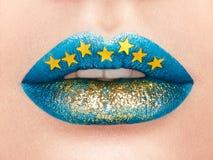 Κλείστε επάνω την άποψη των όμορφων χειλιών γυναικών με το μπλε κραγιόν στοκ εικόνα
