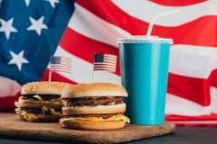 Κλείστε επάνω την άποψη των burgers με τις αμερικανικές σημαίες και το ποτό σόδας Στοκ Εικόνες