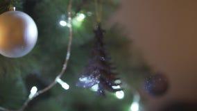 Κλείστε επάνω την άποψη defocus σχετικά με το απίστευτο φωτεινό φως σπινθηρίσματος διακοσμήσεων χριστουγεννιάτικων δέντρων στην ε φιλμ μικρού μήκους