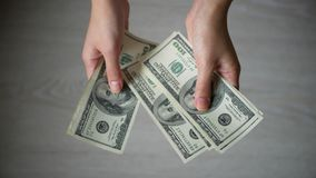 Κλείστε επάνω την αρσενική αρίθμηση χεριών Φε που εκατό δολάρια τιμολογούν στο γκρίζο υπόβαθρο φιλμ μικρού μήκους