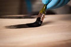 Κλείστε επάνω την εικόνα του χεριού με τη βούρτσα χρωματίζοντας τον ξύλινο πίνακα Στοκ φωτογραφίες με δικαίωμα ελεύθερης χρήσης