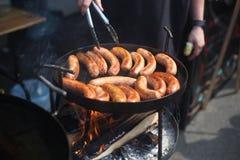 Κλείστε επάνω την εικόνα των λουκάνικων χοιρινού κρέατος που μαγειρεύουν στη σχάρα Τρόφιμα οδών στοκ εικόνες