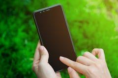 Κλείστε επάνω την εκμετάλλευση χεριών γυναικών και σχετικά με την οθόνη στη σύγχρονη μαύρη χλεύη smartphone επάνω στην κάθετη θέσ στοκ φωτογραφία με δικαίωμα ελεύθερης χρήσης