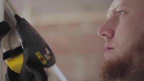 Κλείστε επάνω την επαγγελματική ικανότητα πορτρέτου craftman στα μαύρα γάντια βάζοντας την κόλλα στο ξύλινο πλαίσιο για τον καθρέ απόθεμα βίντεο