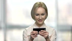 Κλείστε επάνω την επιχειρησιακή γυναίκα που παίζει το τηλεοπτικό παιχνίδι φιλμ μικρού μήκους