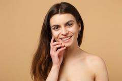 Κλείστε επάνω την ημίγυμνη δεκαετία του '20 γυναικών brunette με το τέλειο δέρμα, nude αποτελέστε απομονωμένος στο μπεζ υπόβαθρο  στοκ φωτογραφίες