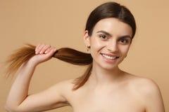 Κλείστε επάνω την ημίγυμνη δεκαετία του '20 γυναικών brunette με το τέλειο δέρμα, nude αποτελέστε απομονωμένος στο μπεζ υπόβαθρο  στοκ εικόνες
