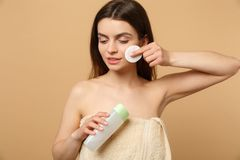 Κλείστε επάνω την ημίγυμνη δεκαετία του '20 γυναικών brunette με το τέλειο δέρμα, η αφαίρεση nude αποτελεί απομονωμένος στο μπεζ  στοκ εικόνα με δικαίωμα ελεύθερης χρήσης