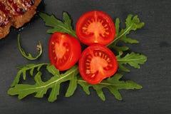 Κλείστε επάνω την ντομάτα και το arugula κερασιών στον πίνακα πλακών Στοκ Φωτογραφία