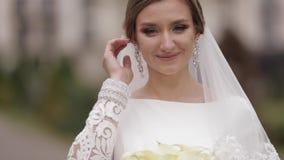 Κλείστε επάνω την όμορφη νύφη στο κομψό γαμήλιο φόρεμα έξω Γοητευτική τοποθέτηση γυναικών στη κάμερα απόθεμα βίντεο