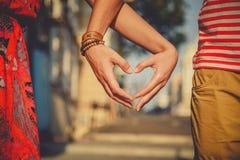 Κλείστε επάνω της αγάπης του ζεύγους που κάνει τη μορφή καρδιών με τα χέρια στην οδό πόλεων Καλοκαίρι στοκ εικόνα