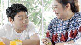 Κλείστε επάνω της ασιατικής μητέρας που ταΐζει στο γιο της ένα κέικ στη διάταξη θέσεων καφέδων απόθεμα βίντεο