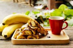 Κλείστε επάνω της γαλλικής φρυγανιάς με τα φρούτα μπανανών και τα κόκκινα φλυτζάνια καφέ στοκ φωτογραφίες με δικαίωμα ελεύθερης χρήσης