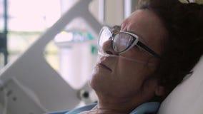 Κλείστε επάνω της γυναίκας ηλικίας φορώντας eyeglasses βρίσκεται σε ένα νοσοκομειακό κρεβάτι με μια μάσκα οξυγόνου σε μια σταλαγμ φιλμ μικρού μήκους