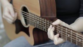 Κλείστε επάνω της γυναίκας που παίζει την κιθάρα, με ένα ρηχό βάθος του τομέα φιλμ μικρού μήκους