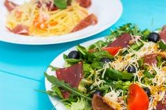 Κλείστε επάνω της εύγευστης σαλάτας στο άσπρο πιάτο στον μπλε ξύλινο πίνακα, Στοκ φωτογραφία με δικαίωμα ελεύθερης χρήσης