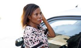 Κλείστε επάνω της κλίσης γυναικών ενάντια σε ένα άσπρο αυτοκίνητο στοκ φωτογραφία