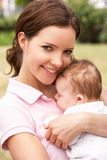 Κλείστε επάνω της μητέρας που αγκαλιάζει το νεογέννητο αγοράκι Outdo Στοκ εικόνες με δικαίωμα ελεύθερης χρήσης