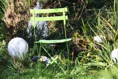 Κλείστε επάνω της μόνης απομονωμένης πράσινης ξύλινης διπλώνοντας καρέκλας στον κήπο με τις χλόες, πράσινος κάλαμος, ηλεκτρικοί σ στοκ φωτογραφία με δικαίωμα ελεύθερης χρήσης