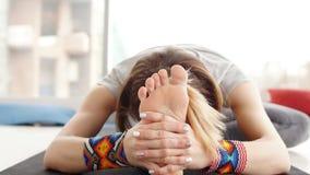 Κλείστε επάνω της νέας γιόγκας άσκησης γυναικών, καθμένος στο κεφάλι στο γόνατο κάμψτε προς τα εμπρός την άσκηση φιλμ μικρού μήκους