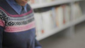 Κλείστε επάνω της νέας γυναίκας αφροαμερικάνων διαβάζει τη συνεδρίαση βιβλίων στο πάτωμα στην πανεπιστημιακή βιβλιοθήκη απόθεμα βίντεο