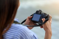 Κλείστε επάνω της νέας γυναίκας με τη κάμερα που εξετάζει την οθόνη στοκ φωτογραφία