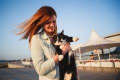 Κλείστε επάνω της νέας γυναίκας με το κράτημα μιας γάτας στον ξύλινο θερινό χρόνο γεφυρών στοκ εικόνες με δικαίωμα ελεύθερης χρήσης