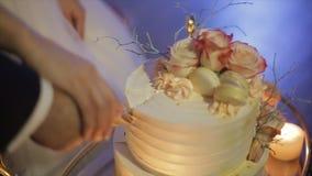 Κλείστε επάνω της νύφης και του νεόνυμφου που κόβουν το γαμήλιο κέικ τους απόθεμα βίντεο