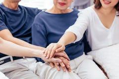 Κλείστε επάνω της οικογένειας με τα ενήλικα παιδιά και η ανώτερη τοποθέτηση γονέων δίνει μαζί να καθίσει στον καναπέ στο σπίτι απ στοκ φωτογραφία με δικαίωμα ελεύθερης χρήσης