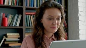 Κλείστε επάνω της σγουρής νέας γυναίκας στα γυαλιά που λειτουργούν στη συσκευή ταμπλετών και που χαμογελούν στη κάμερα στη βιβλιο απόθεμα βίντεο