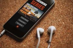 Κλείστε επάνω της σειράς app ροής σε μια κινητή τηλεφωνική οθόνη, κοντά στα άσπρα ακουστικά σε έναν καφετή πίνακα Στοκ εικόνες με δικαίωμα ελεύθερης χρήσης