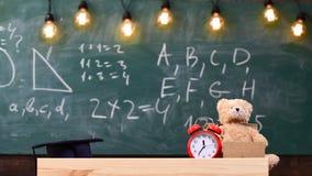 Κλείστε επάνω της τάξης δημοτικών σχολείων Τάξη με τον πίνακα κιμωλίας στο υπόβαθρο Παιδαριώδες γραφείο με το ξυπνητήρι και teddy Στοκ Εικόνα
