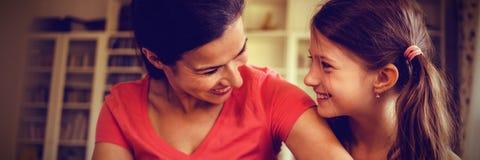 Κλείστε επάνω της χαμογελώντας μητέρας και της κόρης που εξετάζουν η μια την άλλη στοκ εικόνες
