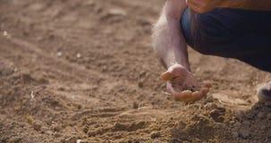 Κλείστε επάνω της Farmer εξετάζοντας την εδαφολογική ποιότητα στο φρέσκο καλλιεργημένο τομέα απόθεμα βίντεο